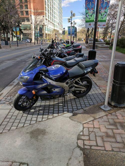dviračiai,vasaros gatvė,motociklai,automobilių stovėjimo aikštelė,stovintys dviračiai,gatvės dviračiai,dviračių eilė,vasara