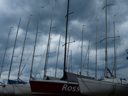 valtys,uostas,burlaiviai,stiebai,valčių stiebai,burių stiebai,niūrus,tamsi,srutos,dangus,debesuotumas,audra