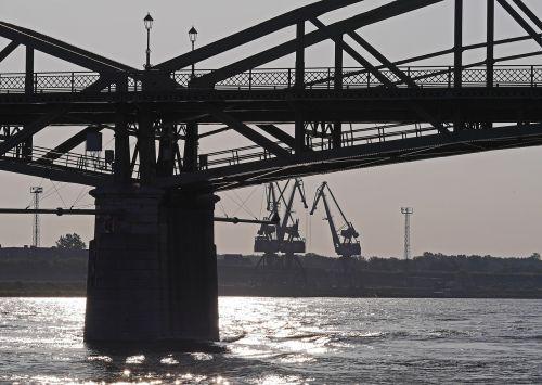 tiltas,kranai,uostas,Danube,ryto šviesa,apakinti,atgal šviesa,dabartinis,upė,plačiajuostis ryšys,vežėjas,kelio,turėklai,kranas,vanduo,apmąstymai,slovakija,žibintai,santūra,uosto kranai,vidaus vandens kelių transportas,transportas,Logistika,srautas,ramstis,dabartinis ramstis,Boko kranas,technologija,grafika,atmosfera,veidrodis,kruizas,upės kruizas,kruizas danube,Danube tiltas