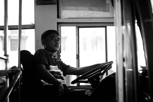 autobuso vairuotojas,autobuso vairuotojas,gatvių fotografija,juoda ir balta,vairuoja