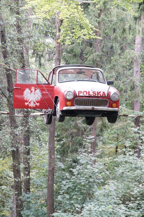 automobilis,transporto priemonė,skraidantis automobilis,miškas,Lenkija,automobilis ant styginių,kabantis automobilis,juokingas automobilis,syrenka,raudona mašina,Eagal simbolis,Lenkijos simboliai