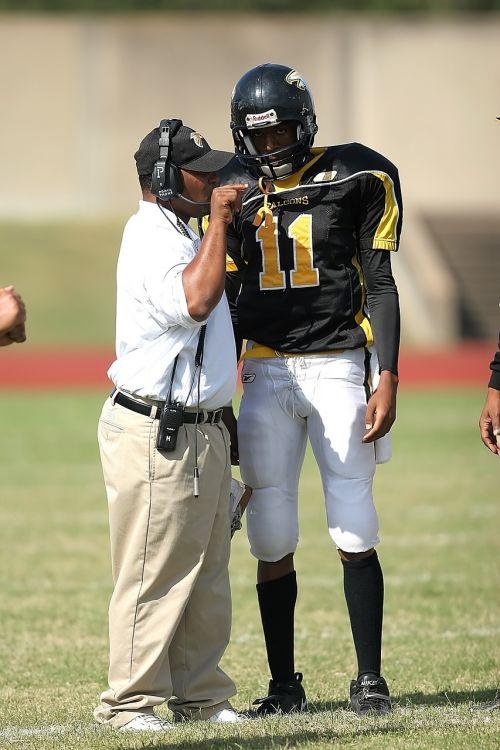 treneris,instruktavimas,futbolo treneris,amerikietiškas futbolo treneris,vidurinės mokyklos treneris,futbolas,amerikietiškas futbolas,kryptys,futbolininkas,amerikietiškas futbolininkas,žaidimas,varzybos,Sportas,komanda,sportininkas,uniforma,šalmas,galvos rinkinys,komunikacija,vyras,instrukcija,Teksaso vidurinės mokyklos futbolas