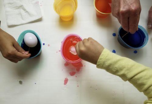 Velykų & nbsp, kiaušinis, dažymas, šeima, vienas suaugęs, du & nbsp, vaikai, nėra veidų, peržiūrėkite & nbsp, iš & nbsp, aukščiau, spalvos, purslai, dažymas & nbsp, puodeliai, maistas & nbsp, dažymas, šeimos spalvos Velykiniai kiaušiniai