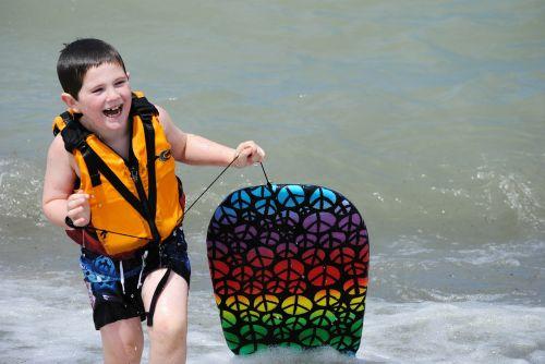 linksma,žaisti,banglenčių sportas,maudytis,maudytis,laimingas,vanduo,berniukas,vaikas,vaikai,šypsena