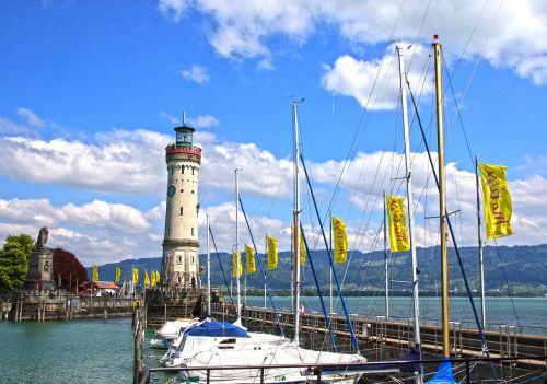lindau,ežero konstanta,uostas,švyturys,valtys,burlaiviai,vėliavos,dangus,mėlynas,debesys