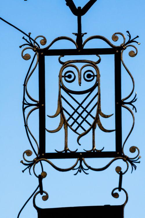 nosies skydas,pelėdos,reklama,reklaminis ženklas,knygynas,išmintis,kalvystė,skydas,auksinis,juoda,stilizuotas,skelbimas,menas,metalas