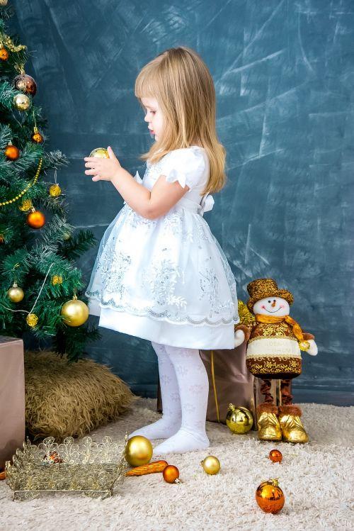 Naujųjų metų vakaras,Kalėdų fonas,šventė,mergina papuošia Kalėdų eglutę,nauji žaislai,Kalėdiniai dekoracijos,naujųjų metų išvakarės,Kalėdos,Kalėdų eglutė,ornamentas,balionai,Kalėdinis kamuolys,papuošalai,auksinis,gražus,atvirukas,pasveikinimas,dekoruoti,dovanos