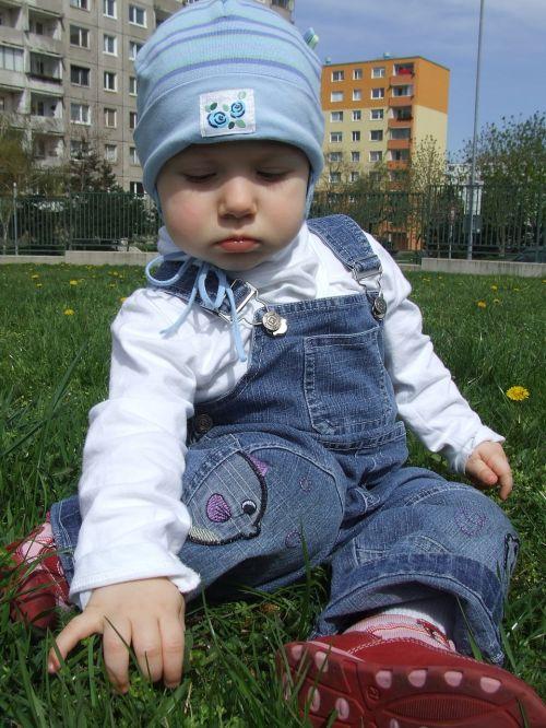berniukas,out,ant žolės,mėlynas dangtelis,sėdėti