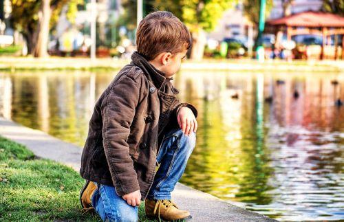 berniukas,vaikas,ežeras,parkas,vaikas žiūri į priekį,berniukas žiūri,vanduo,antis,gamta,kritimas,ruduo,žavinga,žaisti