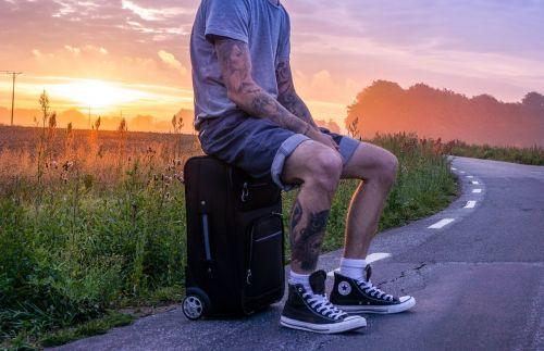 keliautojas,keliautojas,kelionė,klajoti,autostopas,autostopas,vyras,tatuiruotas,tatuiruotės,tatuiruotė,lagaminas,šortai,pasikalbėti,sėdi,banga,kelias